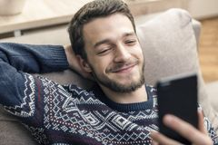 Cheerful young man holding mobile phone and smiling at home. royalty free stock photos