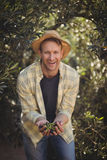 Cheerful young man holding olives while standing by trees at farm Royalty Free Stock Photo