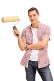 Cheerful young man holding a paint roller Royalty Free Stock Photos