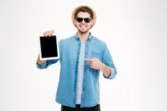 Cheerful young man holding and pointing on blank screen tablet Stock Photography
