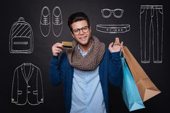 Cheerful young man holding shopping bags and showing discount card. Royalty Free Stock Images