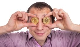 Cheerful young man holds two golden bitcoyne in the eyes stock images