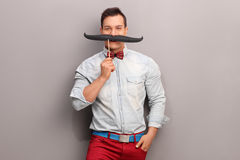 Cheerful young man with a huge fake moustache Royalty Free Stock Photos