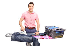 Cheerful young man ironing a pair of jeans Stock Photo