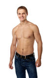 Cheerful young man in jeans with bare torso. Posing against a white background Royalty Free Stock Images
