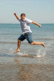 Cheerful young man jumping on the water. Young man jumping for fun on the beach Stock Images