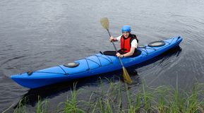 Cheerful young man kayaking on big lake Stock Photo