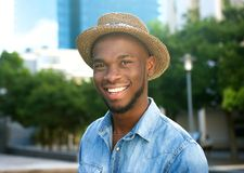 Cheerful young man laughing outdoors with hat Stock Photos