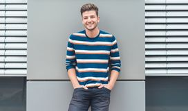 Cheerful young man looking at camera, happy guy leaning to the gray wall stock images