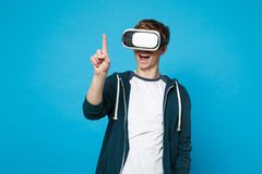 Cheerful young man looking on headset touch something like push click on button, pointing at floating virtual screen. Isolated on blue background. People stock photography