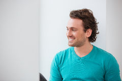 Cheerful young man looking at the window and smiling Royalty Free Stock Photography