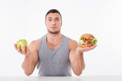 Cheerful young man is making decisions about food Royalty Free Stock Images