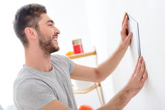 Cheerful young man measuring wall Stock Images