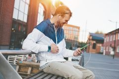 Cheerful young man with mobile phone and headset sitting on the bench. Outdoors Royalty Free Stock Photography