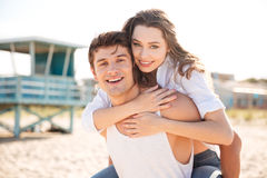 Cheerful young man piggybacking his girlfriend on the beach Royalty Free Stock Photo