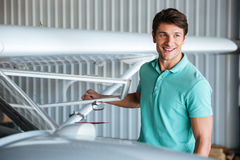 Cheerful young man pilot near small airplane Royalty Free Stock Photo