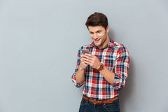 Cheerful young man in plaid shirt standing and using smartphone Royalty Free Stock Images