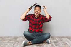 Cheerful young man in plaid sirt holding laptop over head Royalty Free Stock Image