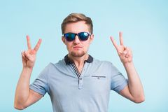 Cheerful young man in polo t-shirt and sunglasses showing victory sign and smiling at camera on blue background.  Royalty Free Stock Photo