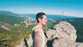 Cheerful young man raising his hands high on top of the big rocky mountain with Cross. Traveler smiles, rejoices and with wide-spread hands rotates the camera stock video footage