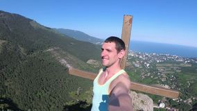Cheerful young man raising his hands high on top of the big rocky mountain with Cross. Traveler smiles, rejoices and with wide-spread hands rotates the camera stock footage