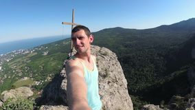 Cheerful young man raising his hands high on top of the big rocky mountain with Cross. Traveler smiles, rejoices and with wide-spread hands rotates the camera stock video