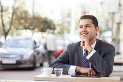 Cheerful young man is resting in cafeteria Royalty Free Stock Images