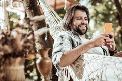 Cheerful young man resting in comfortable hammock