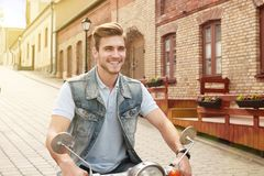 Cheerful young man is riding on scooter in town. Royalty Free Stock Image