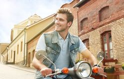 Cheerful young man is riding on scooter in town. Royalty Free Stock Photos