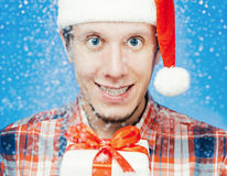 Cheerful young man in santa hat with a gift box Stock Photo