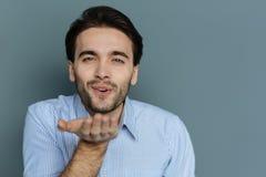 Cheerful young man sending you a kiss stock photos