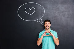 Cheerful young man showing heart by hands Royalty Free Stock Photography