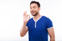 Cheerful young man is showing positive gesture Royalty Free Stock Photography
