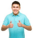 Cheerful young man showing thumb up sign Stock Photography