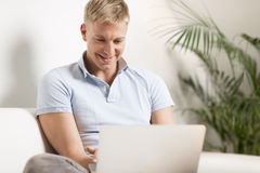 Cheerful young man sitting on couch with laptop. royalty free stock image