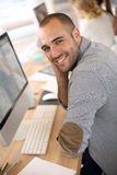 Cheerful young man sitting on desktop computer Royalty Free Stock Image