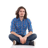 Cheerful young man sitting on the floor with legs crossed. Handsome young man with long hair is sitting on the floor with legs crossed. Full length studio shot Royalty Free Stock Image