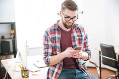 Cheerful young man sitting on the table and using smartphone Stock Photography