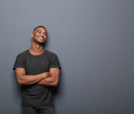 Cheerful young man smiling with arms crossed on gray background. Portrait of a cheerful young man smiling with arms crossed on gray background Royalty Free Stock Photo