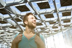 Cheerful young man smiling with bag in airport Stock Photo