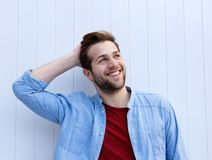 Cheerful young man smiling with hand in hair Royalty Free Stock Photos