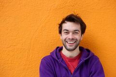 Cheerful young man smiling on orange background Stock Photo
