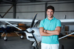 Cheerful young man standing near small plane royalty free stock photos