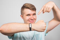 Cheerful young man standing and pointing on fitness tracker over grey background Royalty Free Stock Photography