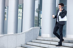 Cheerful young man in suit is using telephone Stock Image