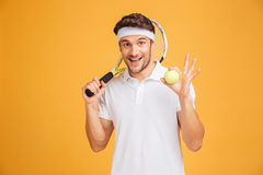 Cheerful young man tennis player holding ball and racket. Over yellow background Stock Images