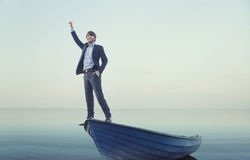Cheerful young man on the tiny boat Royalty Free Stock Image