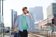 Cheerful young man at train station platform with mobile phone. Portrait of a cheerful young man standing at train station platform with mobile phone stock photo