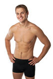 Cheerful young man in trunks over white. Background Stock Images